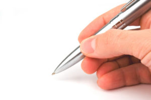 Pen in the hand over white background